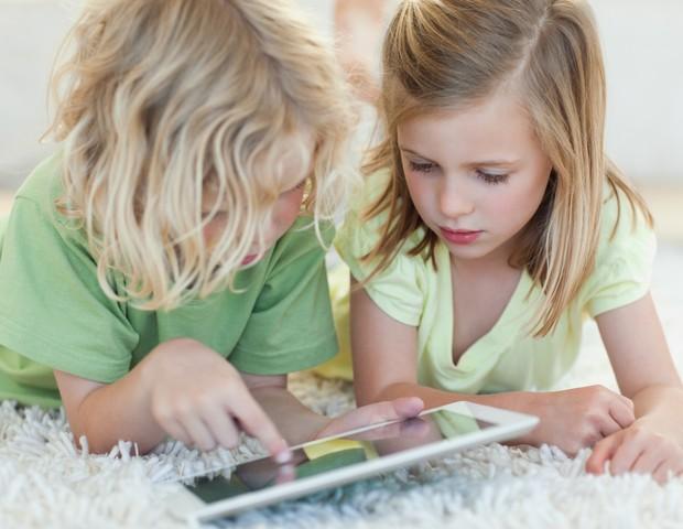 Crianças brincando com iPad no chão (Foto: Shutterstock)