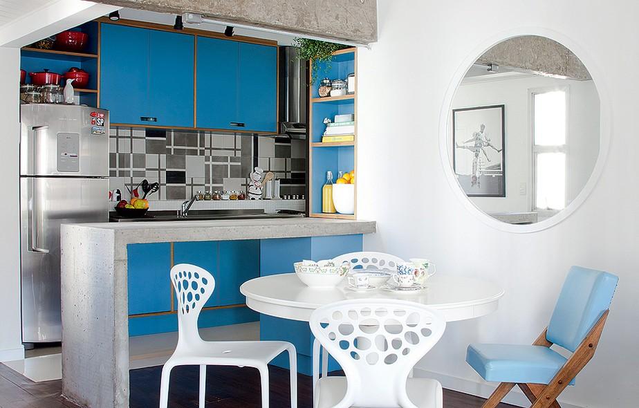 Ao derrubar a parede que fechava a cozinha, a arquiteta Marcela Madureira optou por deixar a viga de concreto sem acabamento. Os ladrilhos hidráulicos instalados sobre a pia foram desenhados por ela