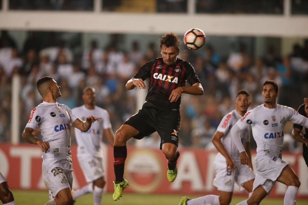 Paulo André, do Atlético-PR, sobe no meio da defesa do Santos para cabecear (Foto: Gazeta do Povo/Albari Rosa)