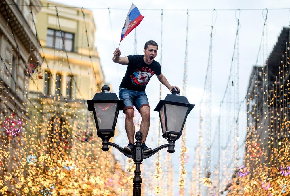 1° de julho - Torcedor da Rússia comemora a vitória no centro de Moscou (Foto: Konstantin Chalabov/AFP)