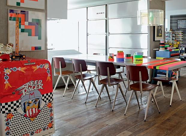 Ainda na casa de Houssein Jarouche, fitas adesivas neon decoram a mesa de jantar. O frigobar tem estampa com desenhos infantis de Adriana Barra (Foto: Otavio Dias/Casa e Jardim)