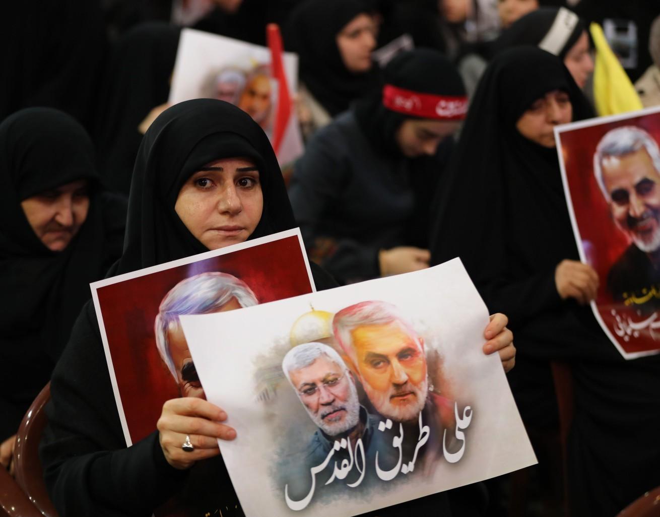 Manifestante carrega cartaz com fotos de Soleimani e comandante Abu Mahdi al-Muhandis