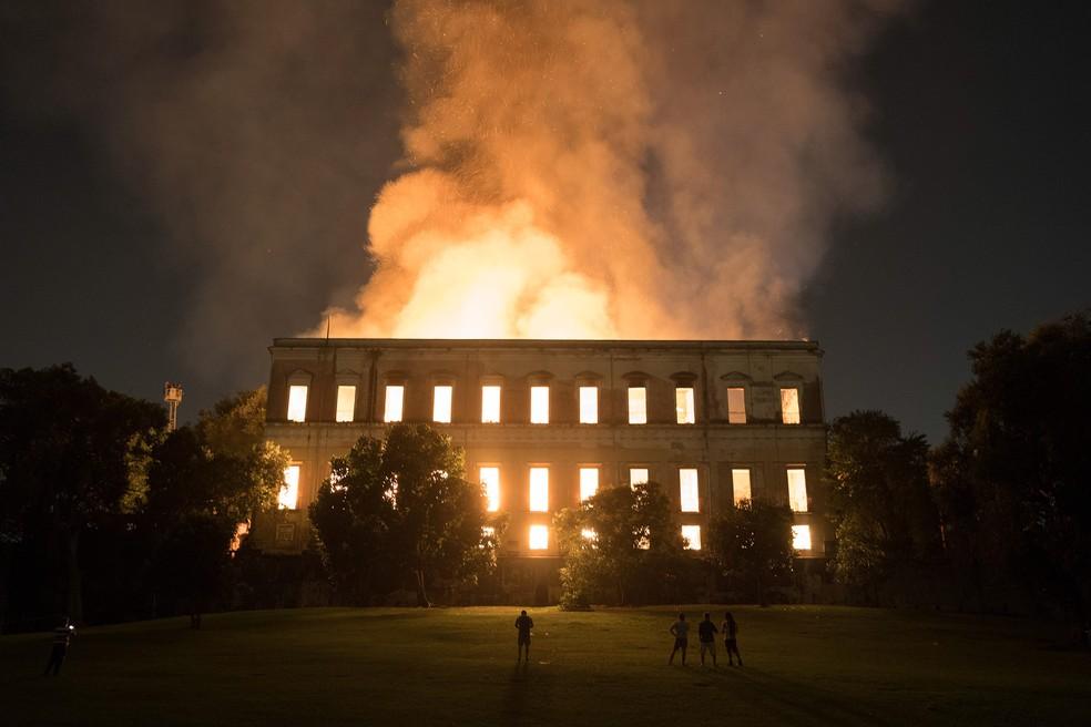 Pessoas observam o incêndio no Museu Nacional, no Rio de Janeiro, na noite de domingo (2) (Foto: Leo Correa/AP)