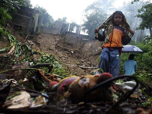 Menino caminha em bairro onde pessoas morreram no desabamento de uma casa após  (Foto: Jacobo Garcia/Reuters)