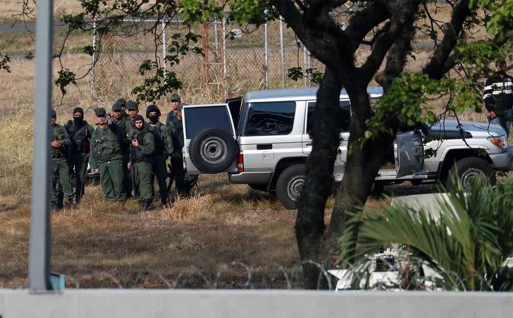 Militares leais a Nicolás Maduro são vistos dentro da base aérea 'La Carlota', em Caracas, apontando para a área onde se reúnem os apoiadores de Guaidó — Foto: Carlos Garcia Rawlins/Reuters
