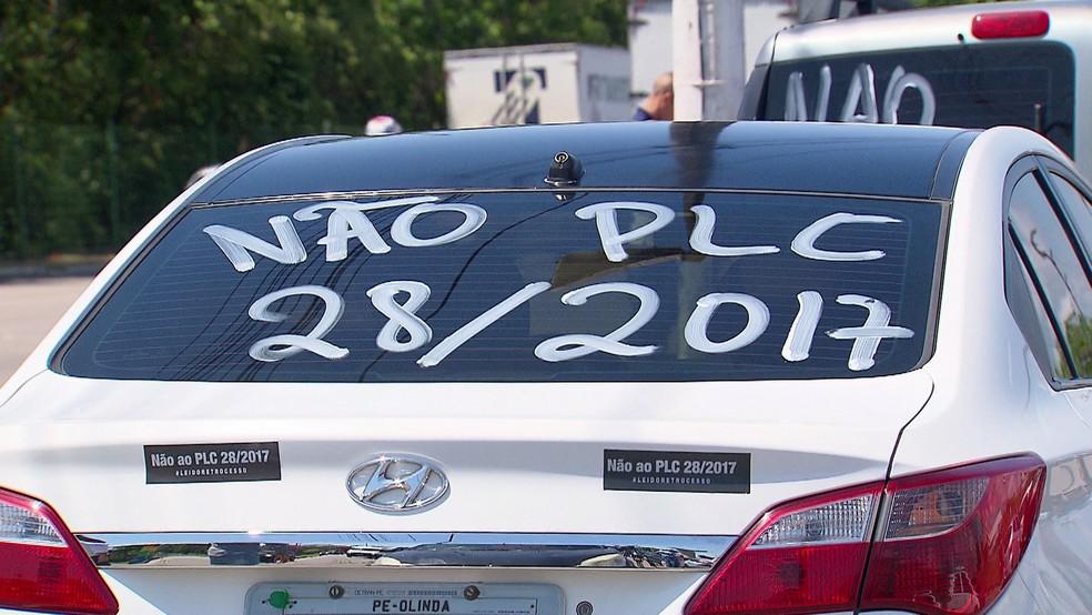 Motoristas do Uber pintam carros para carreata (Foto: Reprodução/TV Globo)