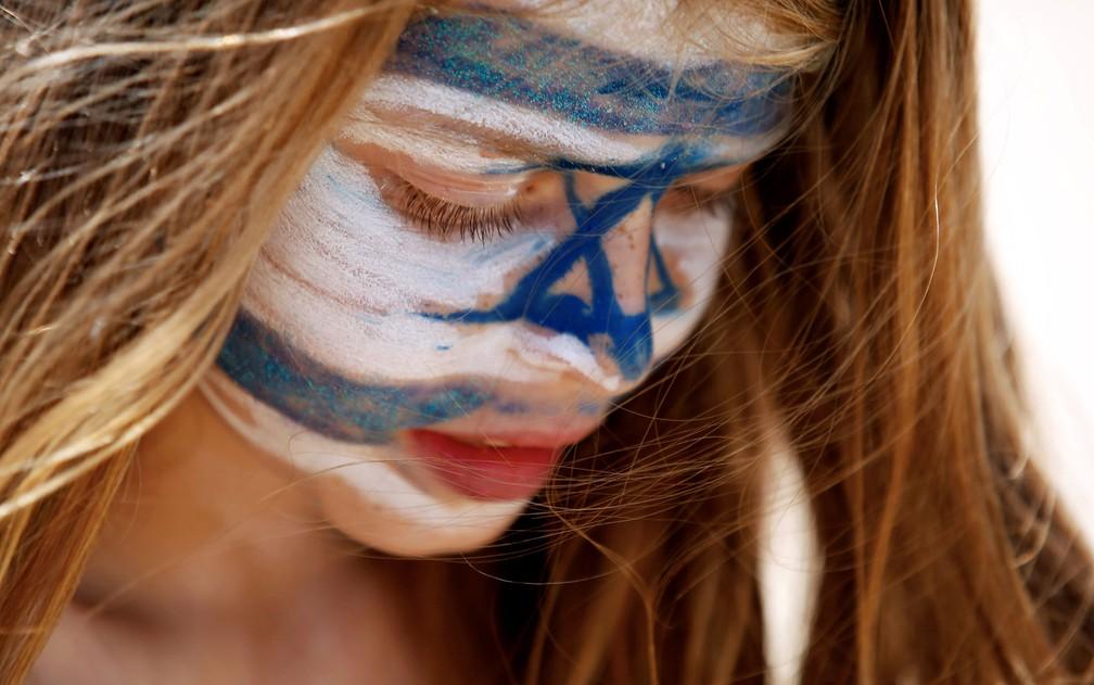 Jovem com a bandeira de Israel pintada no rosto, em Tel Aviv, em foto de 19 de abril (Foto: Reuters/Amir Cohen)