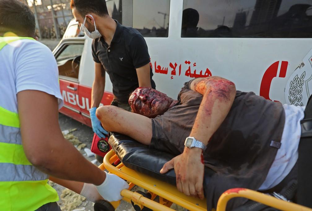 Médicos ajudam homem gravemente ferido no local de explosão em Beirute — Foto: Anwar Amro/AFP