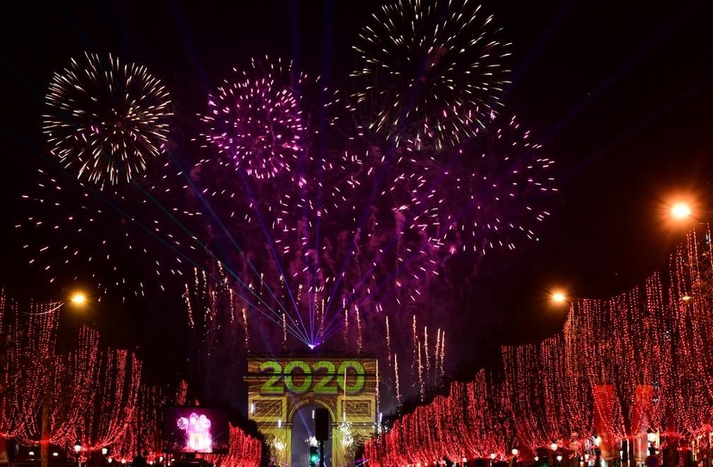 Fogos de artifício iluminam o céu sobre o Arco do Triunfo durante as comemorações do Ano Novo na avenida Champs Elysees, em Paris — Foto: Martin Bureau/AFP