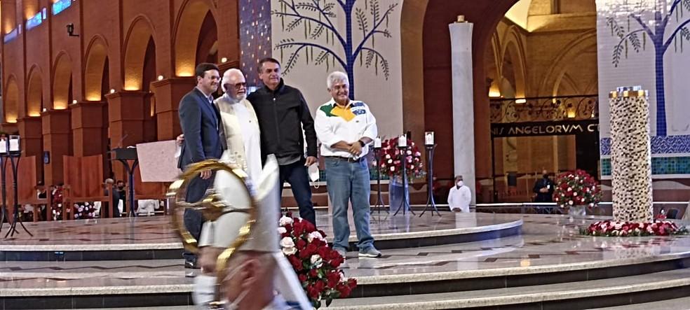 Ao final de missa em Aparecida, Bolsonaro posou sem máscara no altar com os ministros da Cidadania, João Roma, da Ciência e Tecnologia, Marcos Pontes (à direita), e o Padre Américo Dalbelo (ao centro) — Foto: Tiago Bezerra/ TV Vanguarda