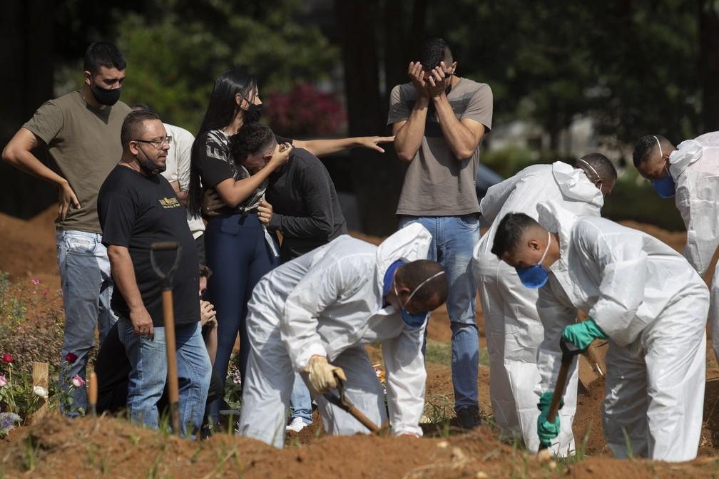 Parentes choram, enquanto mais uma vítima da Covid-19 é enterrada em São Paulo — Foto: Andre Penner/AP Photo