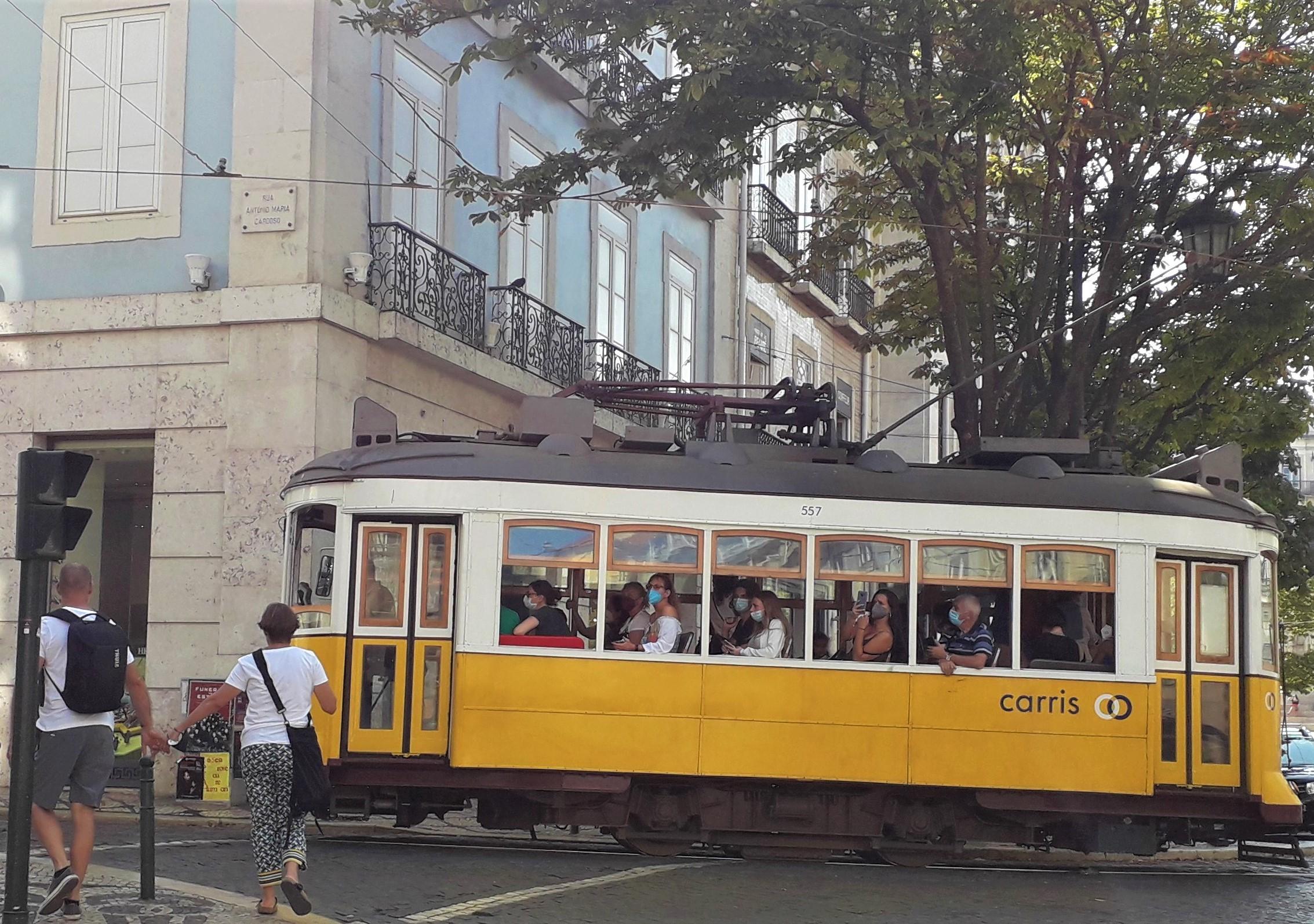 Bondinho com passageiros em uma esquina de Lisboa
