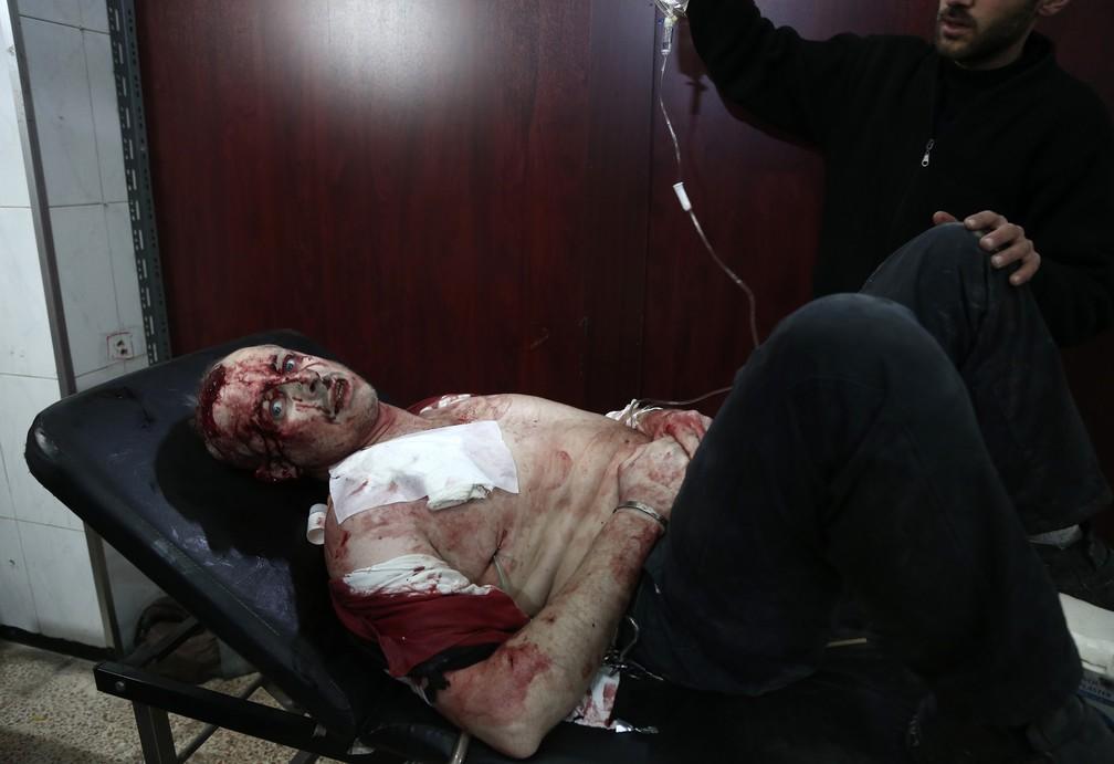 6 de janeiro - Um homem sírio ferido parece estar em choque enquanto espera para receber atendimento em um hospital improvisado, após o bombardeio relatado pelas forças sírias e russas na cidade rebelde de Hamouria, no Ghouta Oriental, na Síria (Foto: Abdulmonam Eassa/AFP)