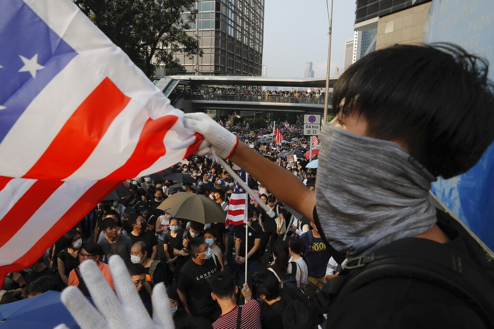 Manifestante com bandeira dos EUA em Hong Kong — Foto: Kin Cheung/AP