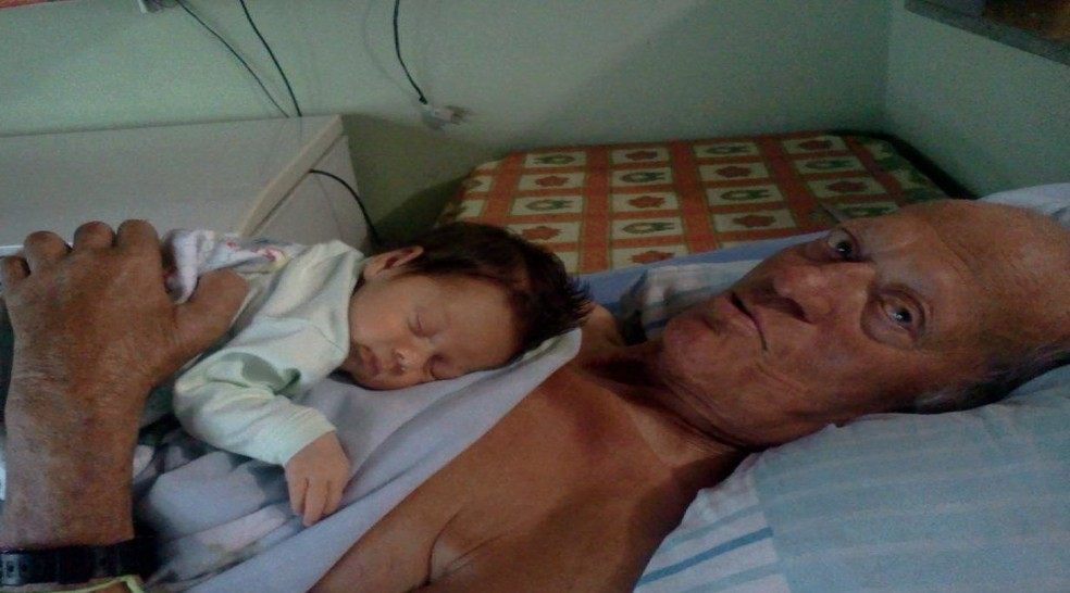 João segura Enzo ainda bebê, o neto cuidador de Santa Gertrudes (Foto: Reprodução/EPTV)