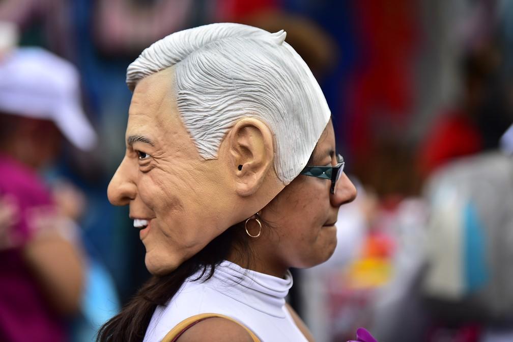 Apoiadora de López Obrador usa máscara do político em evento de campanha na Cidade do México — Foto: Pedro Pardo/AFP