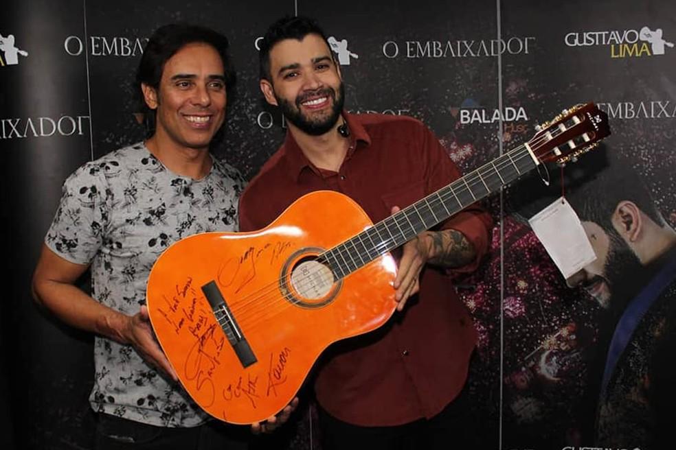 Gusttavo Lima convidou o amigo Guilherme para registrar o momento com o violão, que será leiloado com renda para o Hospital do Câncer de Uberaba — Foto: WEVERTON BARBOSA