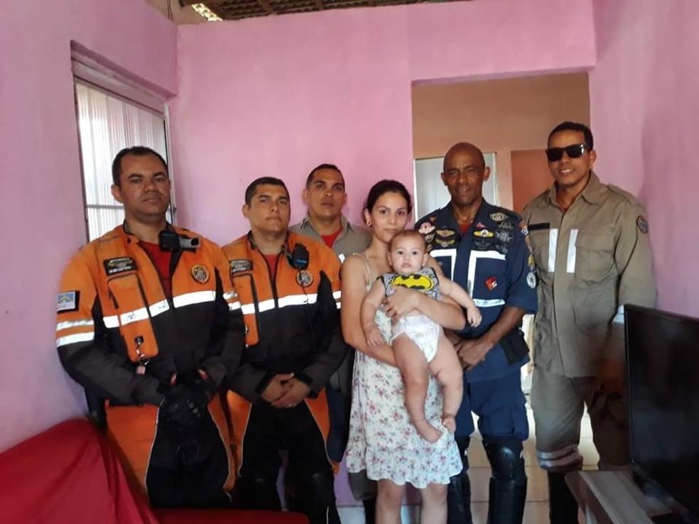 Equipe de bombeiros e a mãe da criança, celebraram o salvamento da criança do bebê de sete meses   (Foto: Corpo de Bombeiros/Divulgação)