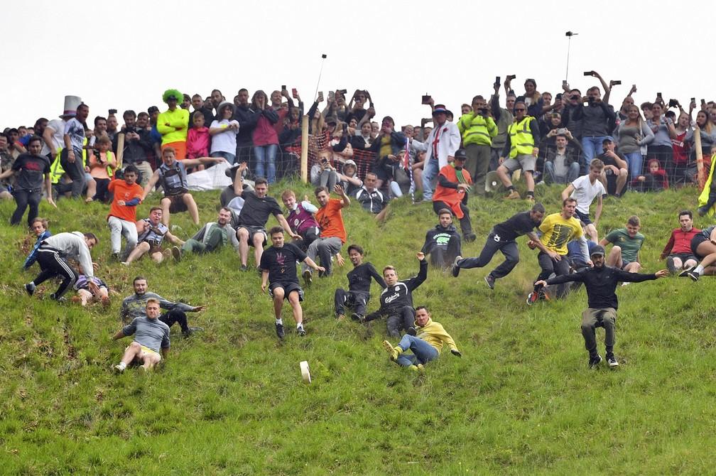 27 de maio - Homens descem correndo a Colina de Cooper em busca de um pedaço de queijo circular durante competição anual realizada em Brockworth, Gloucestershire, na Inglaterra — Foto: Ben Birchall/PA via AP
