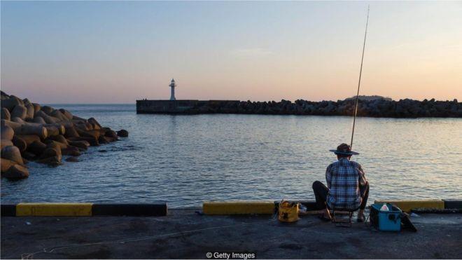 Pescador no porto em Seogwipo, na ilha Jeju, Coreia do Sul (Foto: Getty Images/BBC)