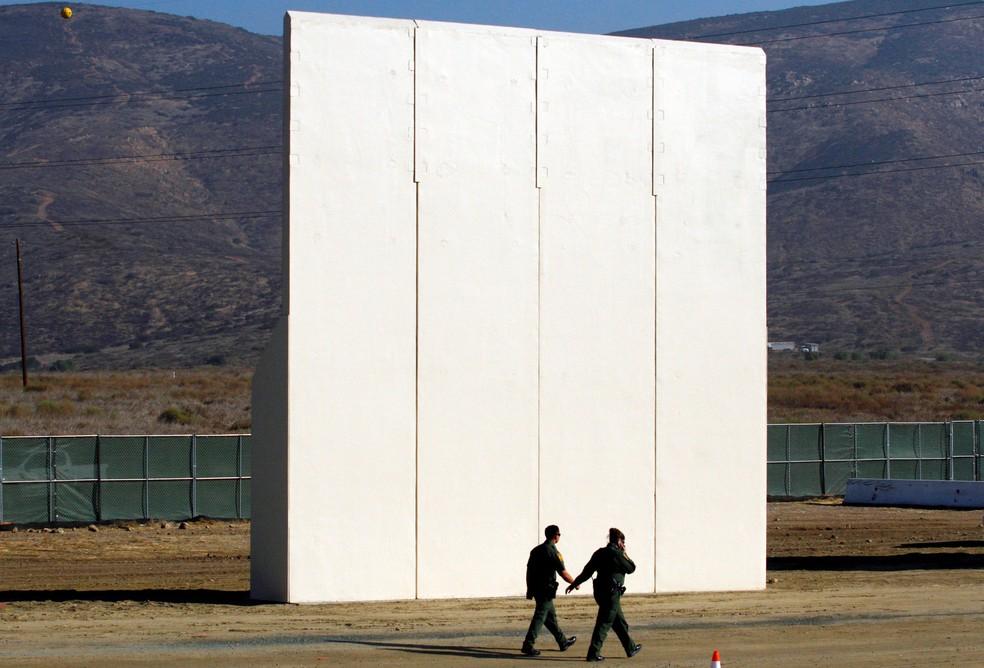 Guardas de patrulha da fronteira dos EUA caminham perto de um protótipo do muro que o presidente dos EUA Donald Trump pretende colocar na fronteira com o México nesta foto tirada do lado mexicano da fronteira, em Tijuana (Foto: Jorge Duenes/Reuters)