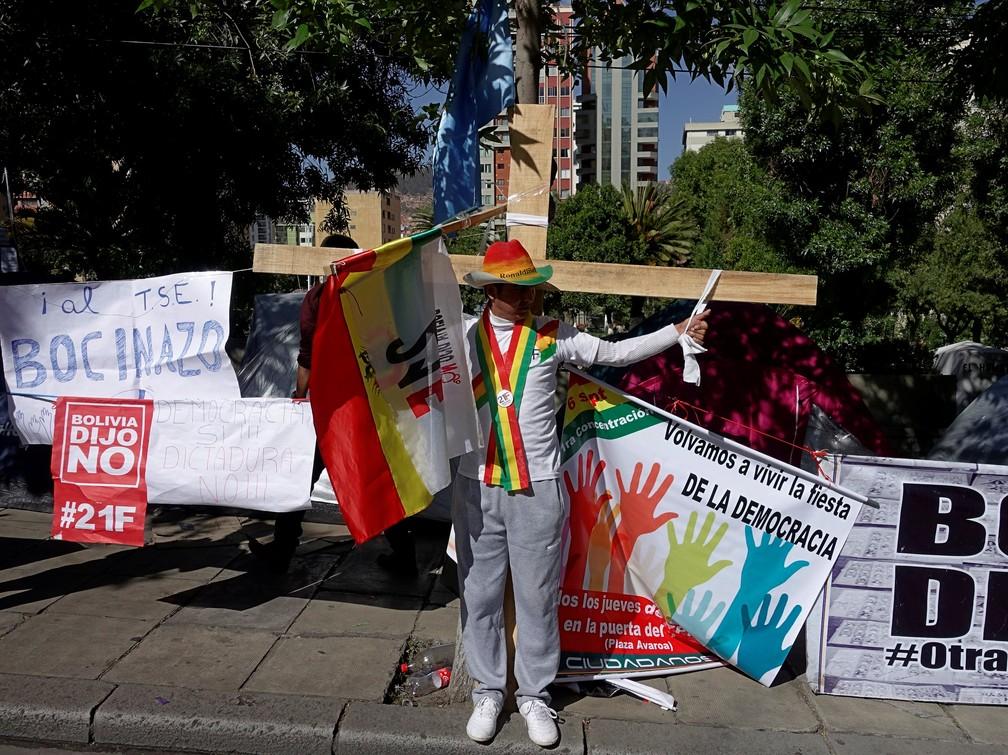 Manifestante com crucifixo protesta na quarta-feira (5) em rua de La Paz contra decisão do TSE de aceitar nova candidatura de Evo Morales à presidência — Foto: David Mercado/Reuters
