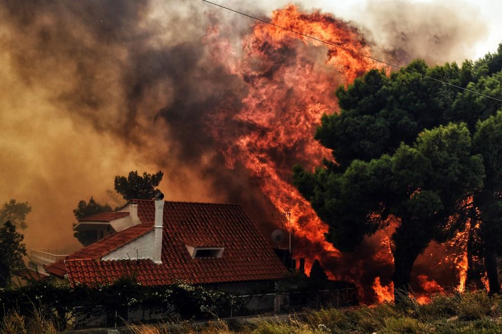 Uma casa é ameaçada pelas chamas de um incêndio florestal em Kineta, perto de Atenas, na Grécia. Mais de 300 bombeiros, 5 aviões e 2 helicópteros trabalham na operação de combate ao fogo (Foto: Valerie Gache/AFP)