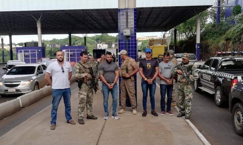 O traficante carioca Capilé - o terceiro da esquerda para a direita da foto - foi expulso do Paraguai e entregue às autoridades brasileiras na aduana da Ponte da Amizade, em Foz do Iguaçu — Foto: Senad-PY/Divulgação