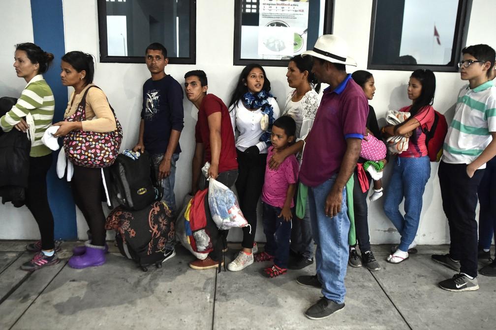 Membros da família Mendoza Landinez entram em fila para pedir status de refugiado em escritório de imigração do Peru, em Tumbes, no dia 25 de agosto (Foto: Luis Robayo/ AFP)