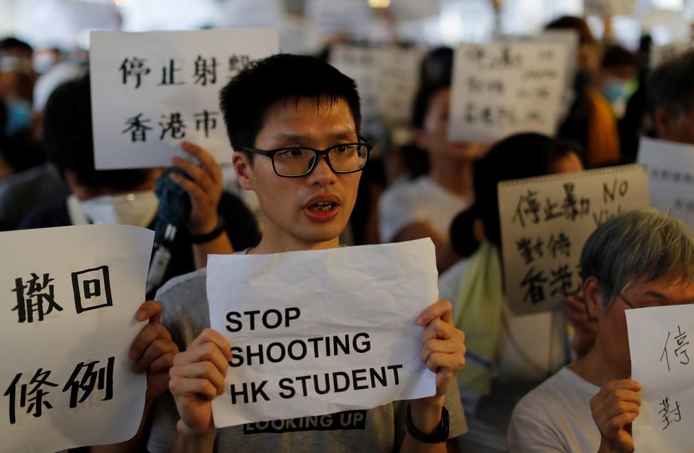 Manifestante segura cartaz pedindo que forças de segurança parem de reprimir os estudantes em Hong Kong nesta quinta (13) — Foto: Reuters/Jorge Silva