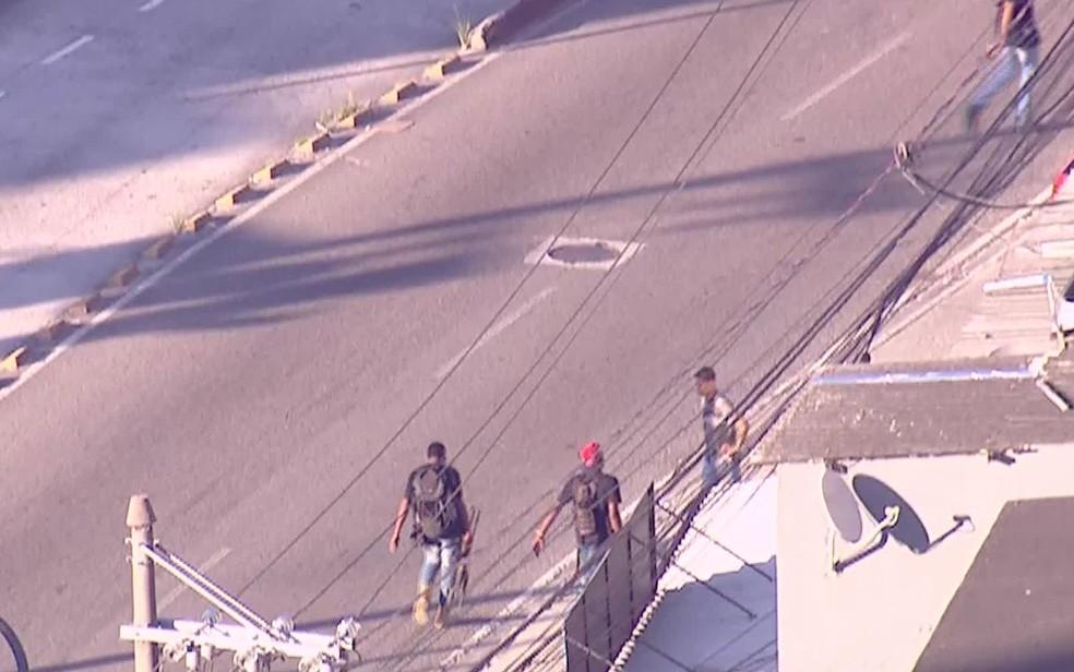 Homens fortemente armados atravessam Rua Cândido Benício (Foto: Reprodução / TV Globo)