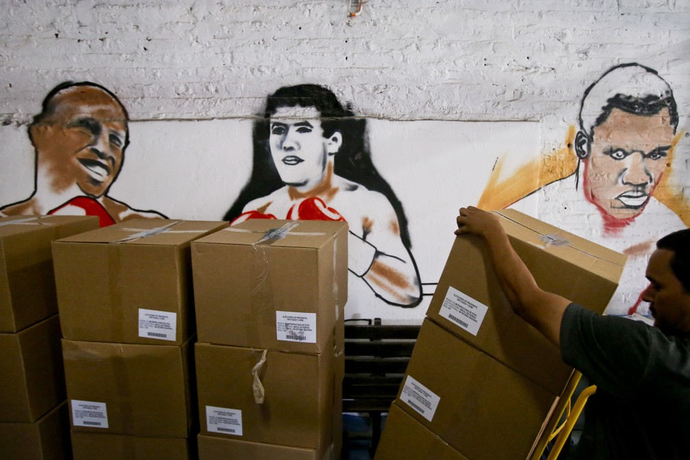 Funcionário eleitoral descarrega material eleitoral para o pleito deste domingo em um estádio na capital Santiago (Foto: Esteban Felix/AP Photo)