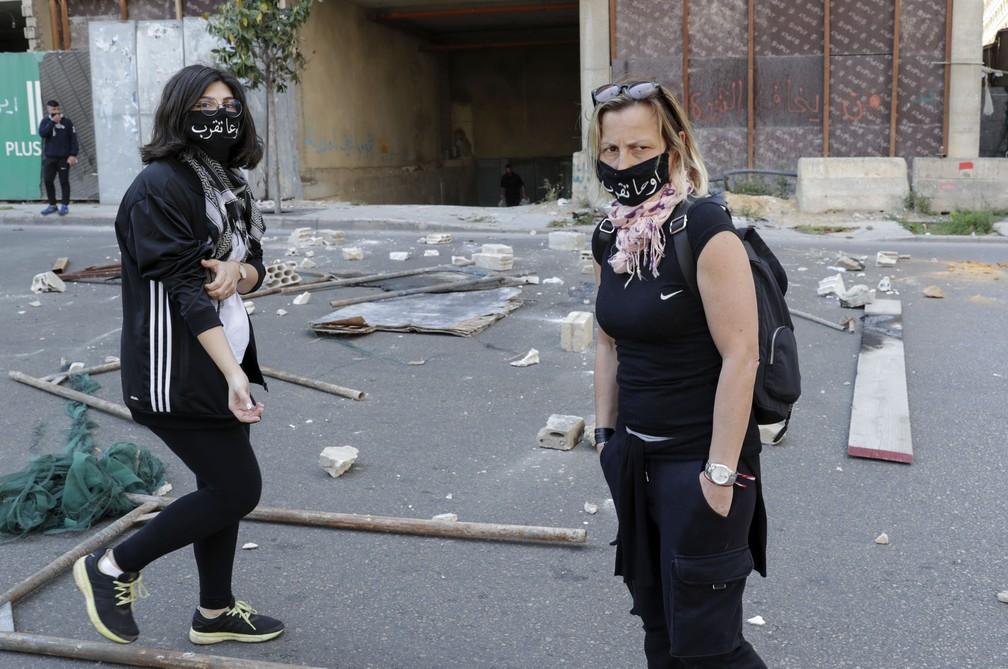 Manifestantes antigovernamentais libaneses usam máscaras protetoras com a inscrição 'nem pensem em se aproximar', durante protesto no centro de Beirute — Foto: Anwar Amro/AFP