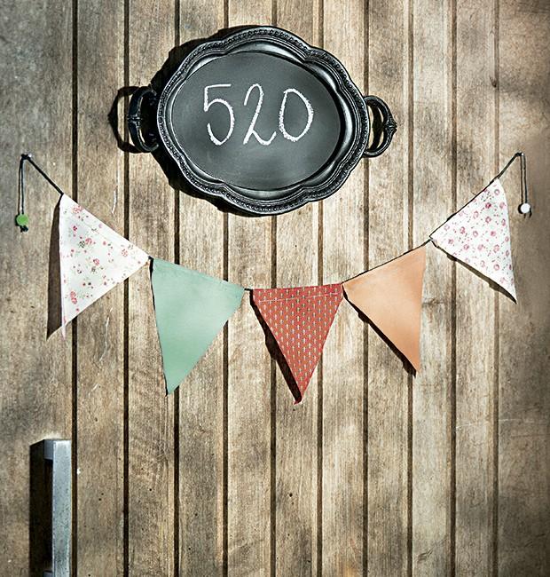 Boas-vindas diferentes: bandeirinhas Botões de Amora na porta e o número da casa escrito na bandeja-lousa Corporação de Ofícios. (Foto: Cacá Bratke/Editora Globo)