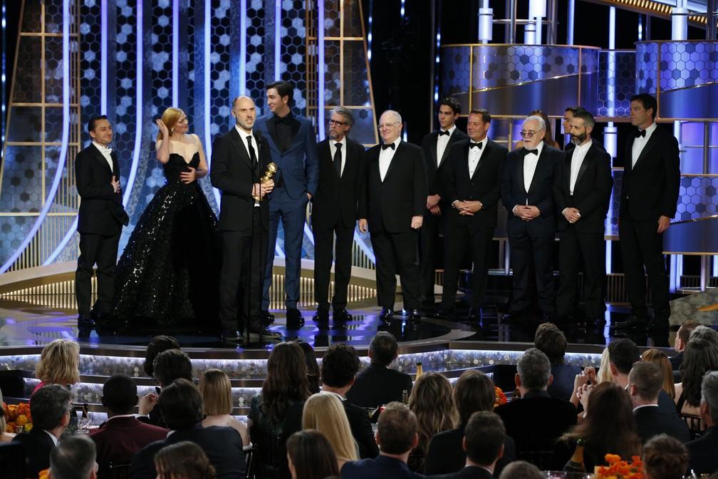 """Equipe e elenco de """"Succession"""" sobe ao palco para receber o Globo de Ouro de melhor série de drama — Foto: Paul Drinkwater/NBC via AP"""