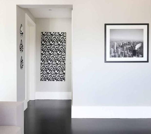 CORREDOR | Tapete da linha Textura da Punto e Filo decora o espaço predominantemente branco com quadros da Moldura Minuto.  (Foto: Mariana Orsi/ Divulgação)