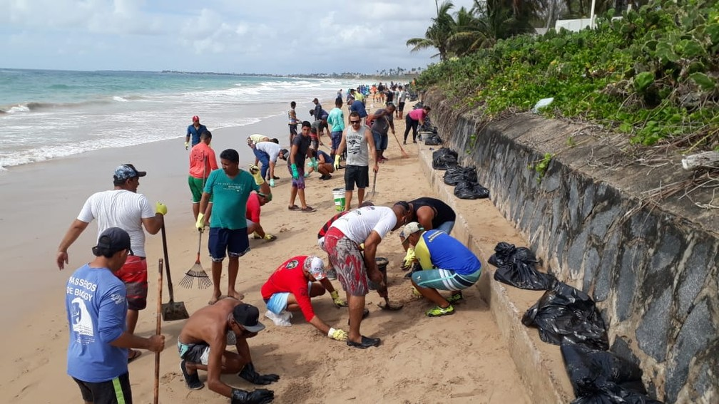 Voluntários limpam óleo encontrado na Praia do Cupe, em Ipojuca, no sábado (19) — Foto: Wellignton Pereira/TV Globo
