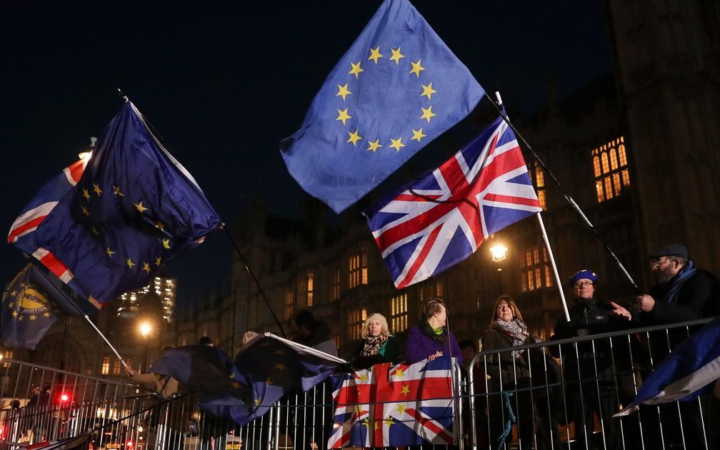 Manifestantes anti-brexit agitam bandeiras do Reino Unido e da União Europeia em frente ao Parlamento, em Londres, na quarta-feira (12) — Foto: Daniel Leal-Olivas/AFP
