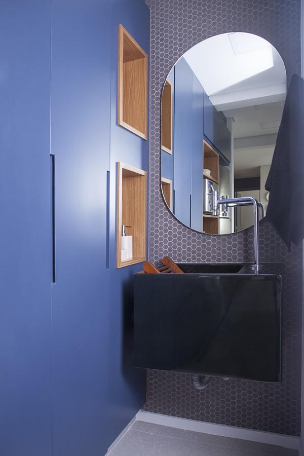 na estilosa lavanderia, tanque preto, espelho e marcenaria azul que camufla a maquina de lavar