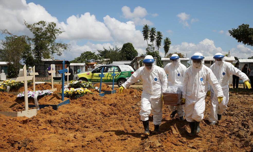 Coveiros carregam caixão, no dia 17 de janeiro, de Jailton de Meneses, 43, que morreu de Covid-19 em Manaus, no cemitério Parque Tarumã. — Foto: Bruno Kelly/Reuters