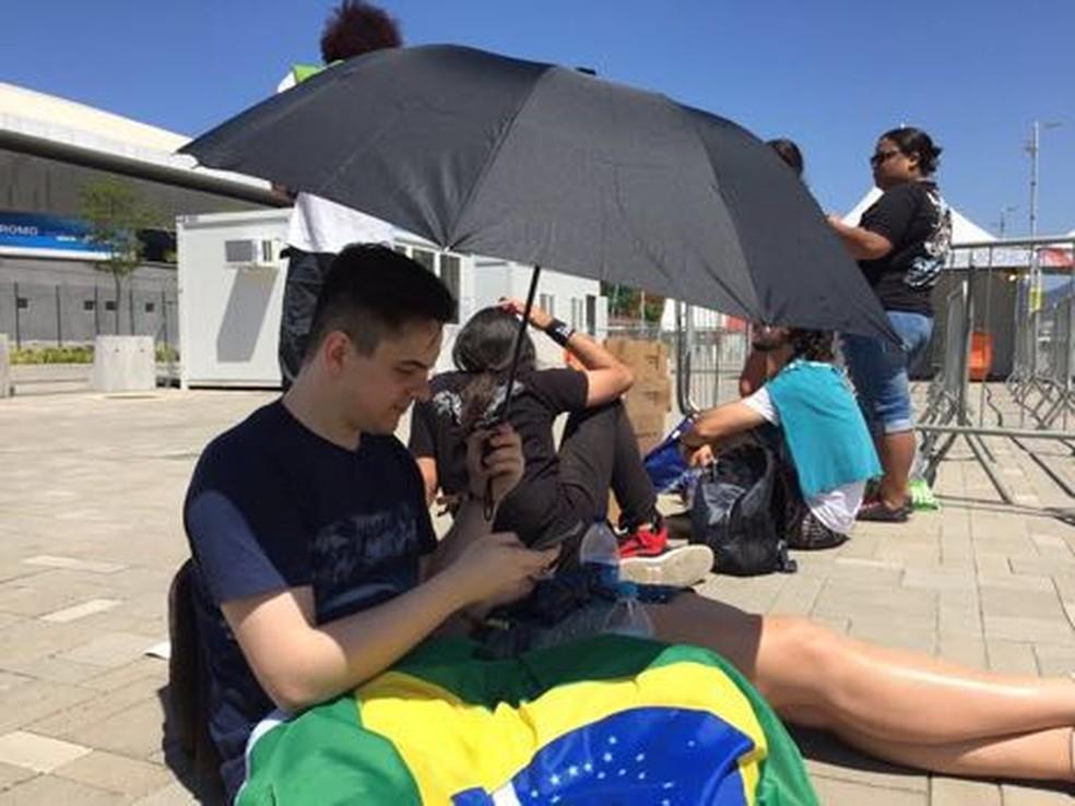 Homem usa guarda-chuva para evitar o sol no Rock in Rio (Foto: Patrícia Teixeira/G1)