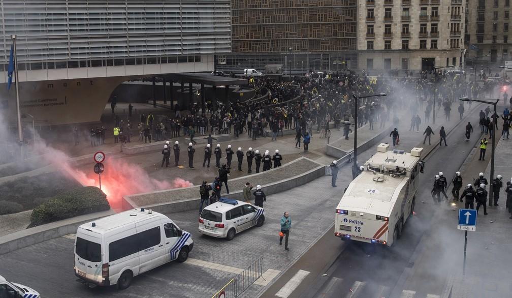 Protestantes enfrentam a polícia durante uma manifestação anti-imigrantes fora da sede da UE em Bruxelas. A polícia usou gás lacrimogêneo e canhões de água para dispersar manifestantes. — Foto: AP / Erik Luntang