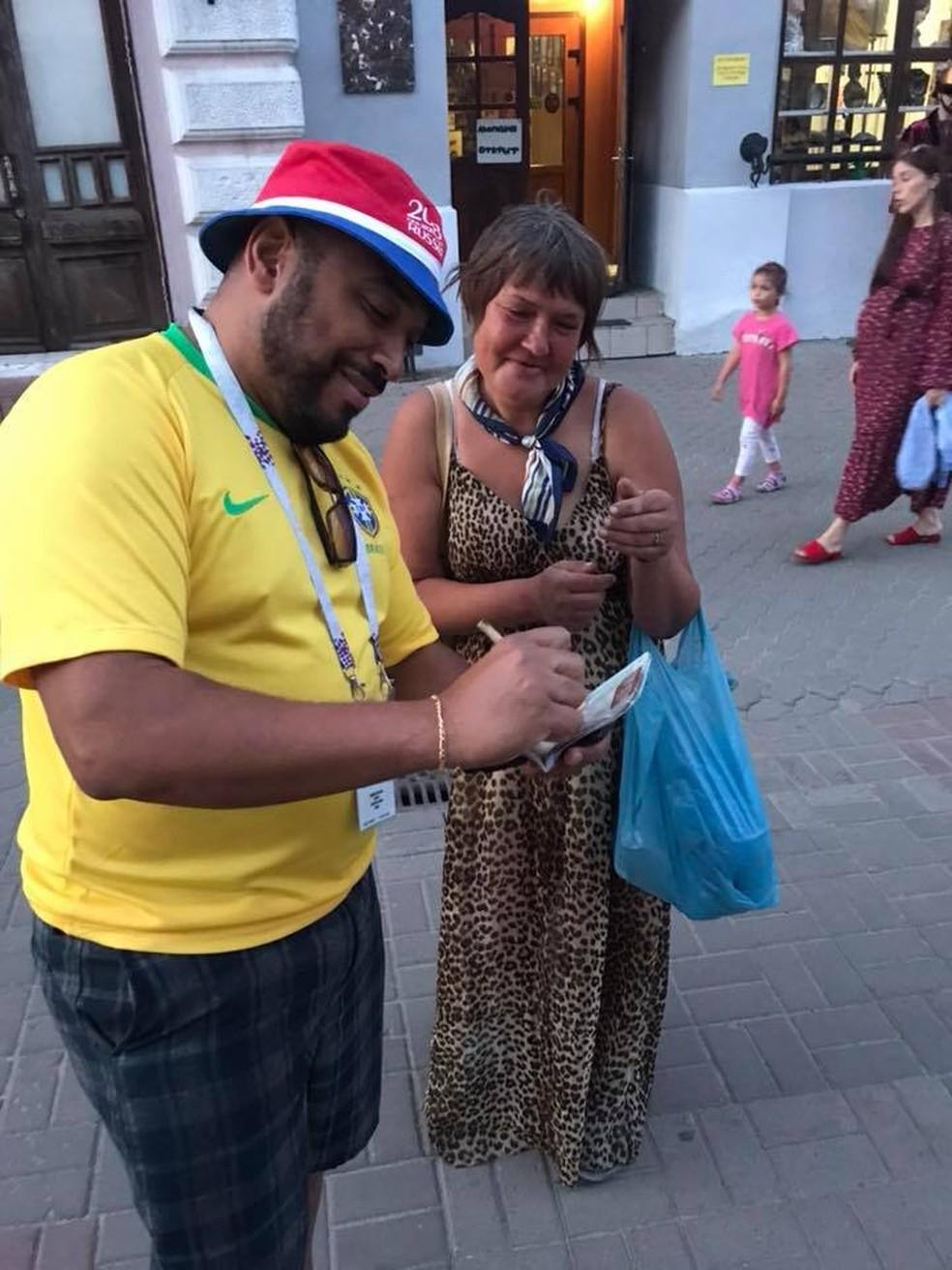 -  Brasileiro Samuel Almeida foi parado por diversos estrangeiros para tirar fotos e dar autógrafos. Na foto acima, ele autografa para uma russa.  Foto: