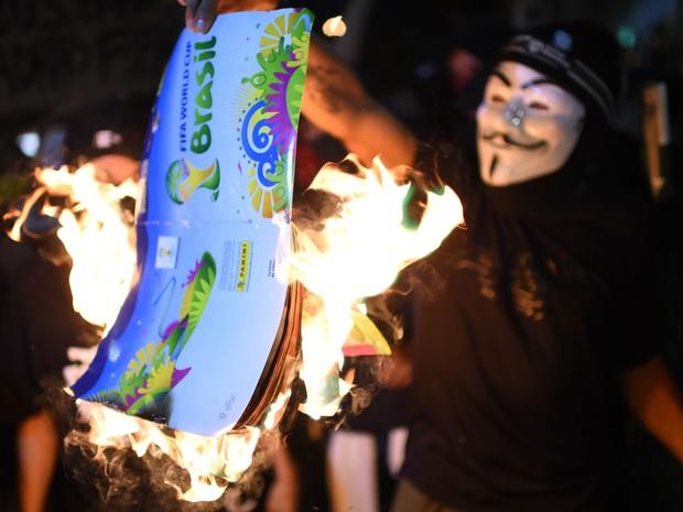 Manifestante queima um papel em formato de ingresso da Copa durante protesto no Rio de Janeiro (Foto: Christophe Simon/AFP)