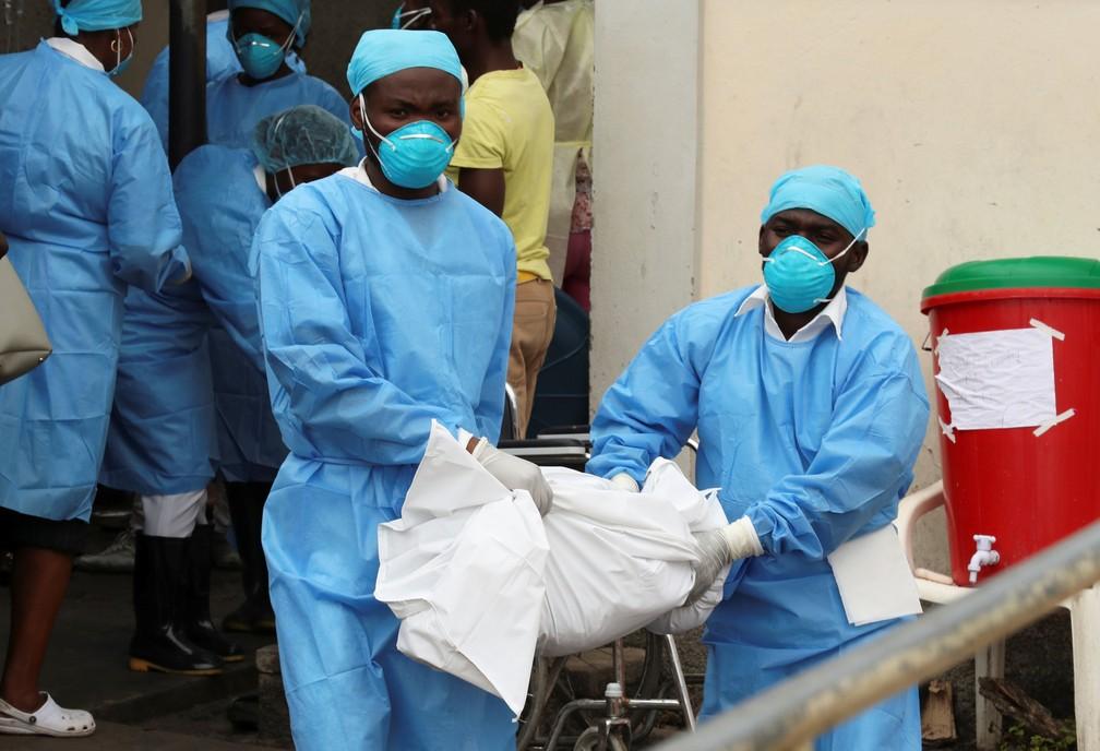 Equipe médica carrega o corpo de uma criança de um ano que morreu em um centro de saúde que trata doenças trazidas pela água em Beira, Moçambique. — Foto: Reuters/Mike Hutchings
