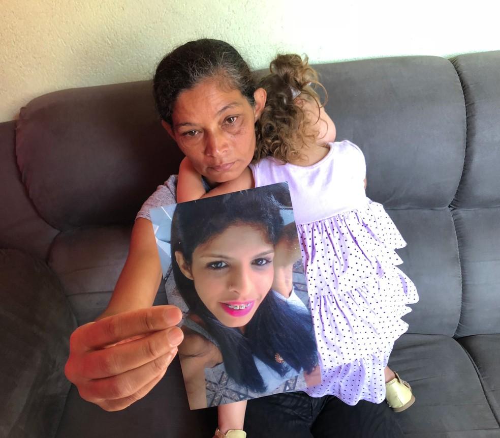 Marlene Maria dos Santos, mãe de Laniele, assassinada pelo marido em Mauá, com a neta no colo e uma foto da filha (Foto: Kleber Tomaz/G1)