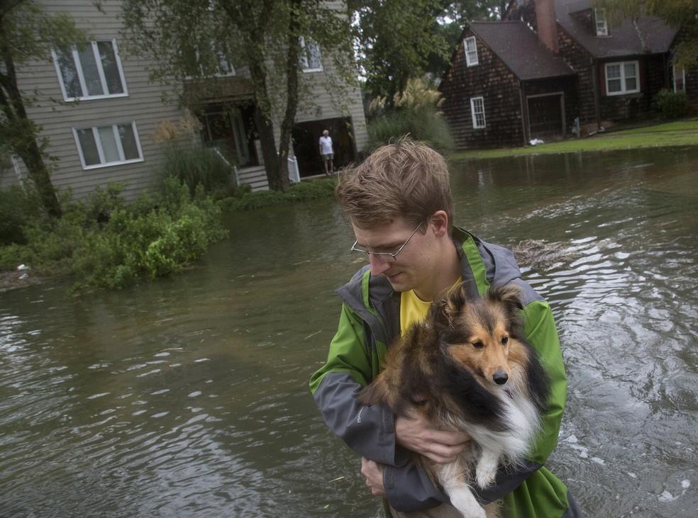 Homem carrega cachorro para atravessar ruas inundadas na cidade de Norfolk, na Virgínia, nos EUA — Foto: Kaitlin McKeown/The Virginian-Pilot via AP