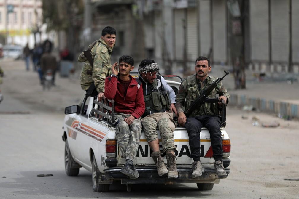Rebeldes do Exército Livre da Síria, apoiados pelas tropas turcas, são vistos nesta segunda-feira (19) em Afrin (Foto: Khalil Ashawi/Reuters)