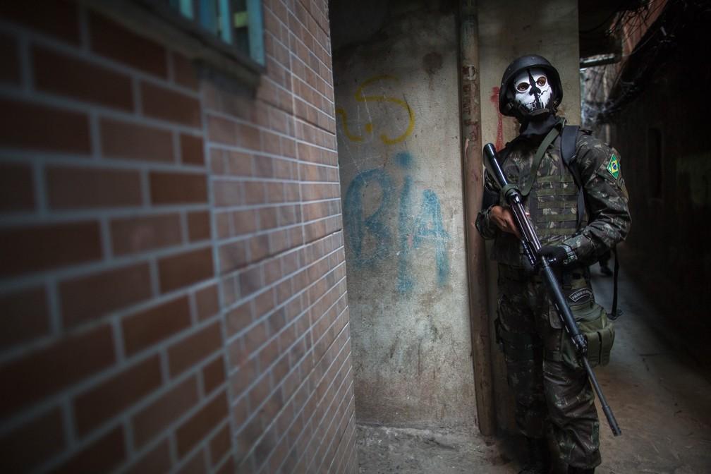Um soldado do exército patrulha um beco na favela da Rocinha, no Rio de Janeiro, nesta segunda-feira (25) (Foto: Mauro Pimetel/AFP)
