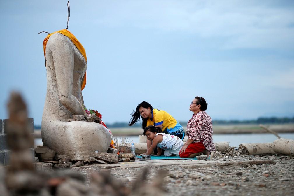 Família reza perto das ruínas de uma estátua de Buda que ressurgiu após seca baixar nível de barragem em Lopburi, na Índia   — Foto: Soe Zeya Tun/ Reuters
